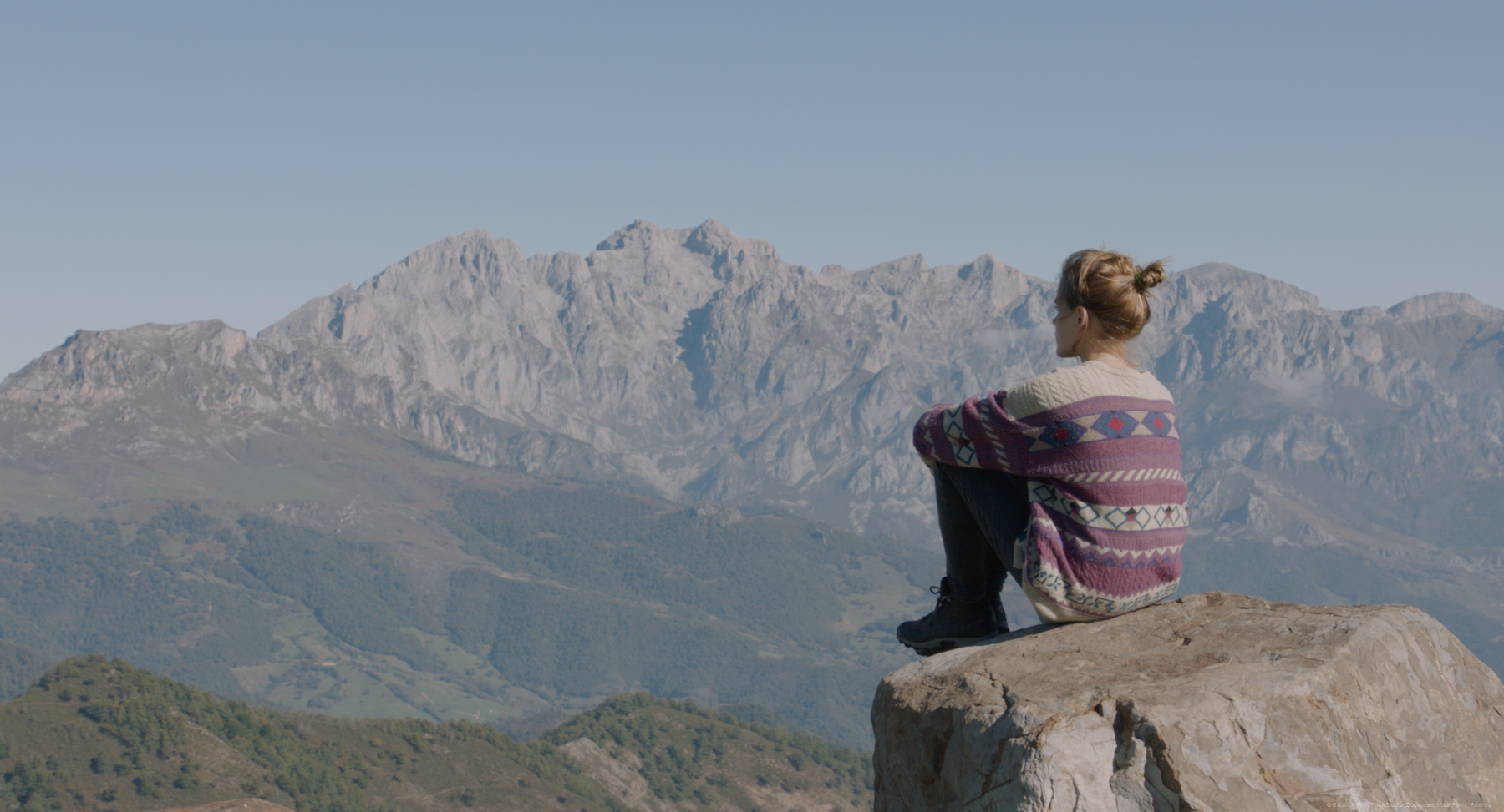 jule-assise-rocher-face-montagne